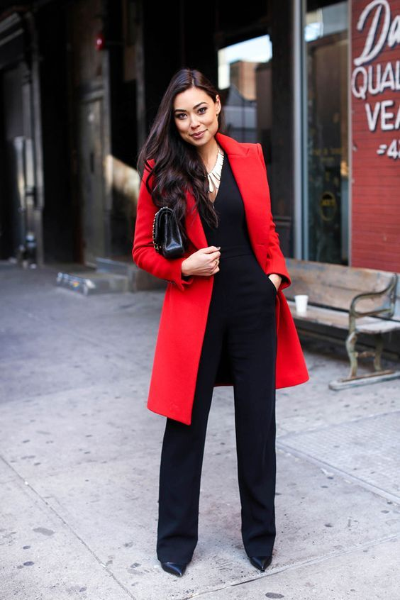 a black jumpsuit, a statement necklace plus a bold red coat is suitable for work