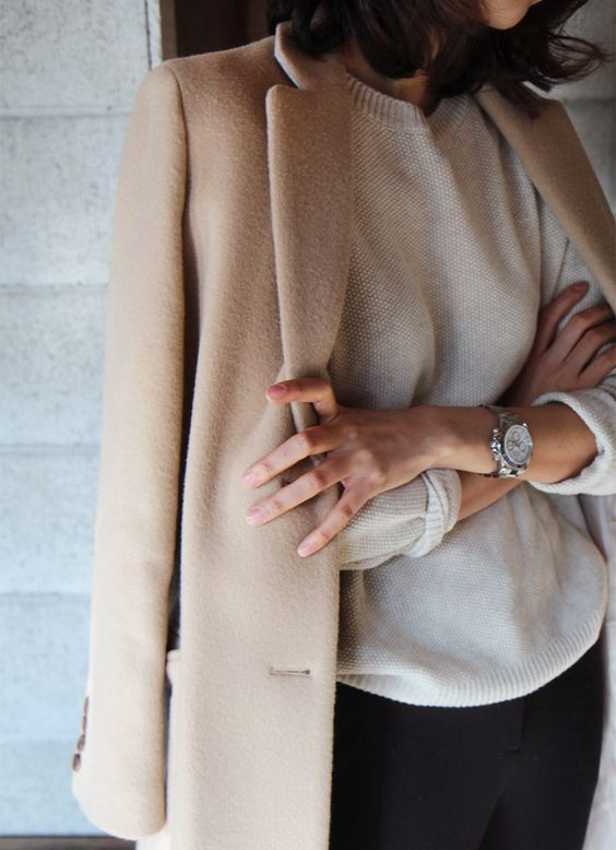 black pants, a white cashmere sweater and a camel coat can be worn to work