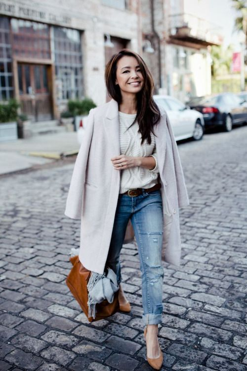 casual winter look with a white cable knit sweater, blue ripped jeans, a cream coat, tan shoes and a matching bag