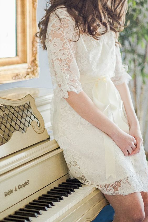 a short off-white lace bridal robe with half sleeves and a silk sash will fit many brides