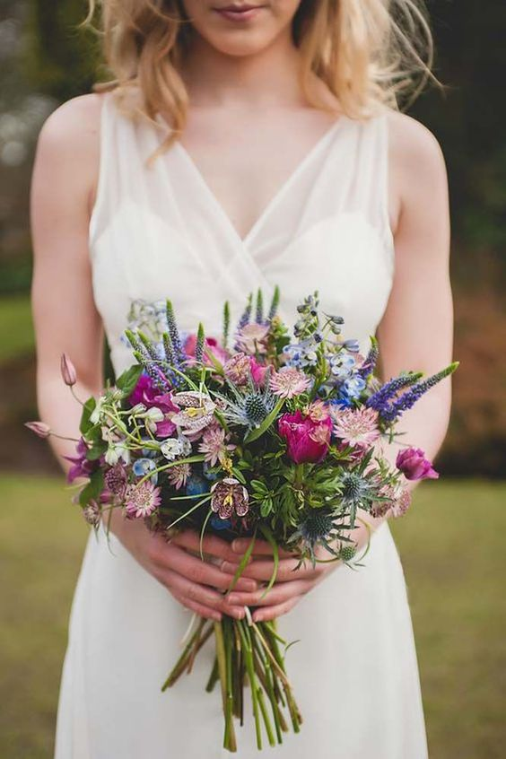 a colorful wildflower wedding bouquet with purple, blue and pink blooms and blue thistles