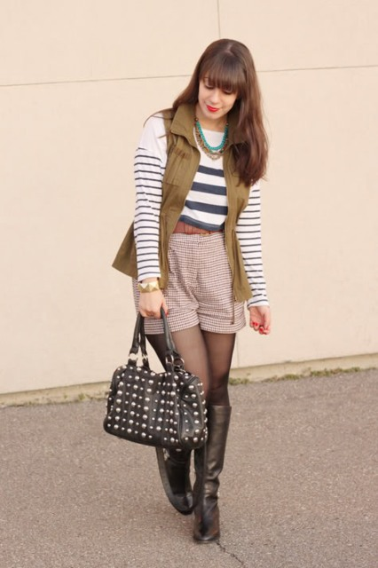 With striped shirt, high boots, olive green vest and black bag