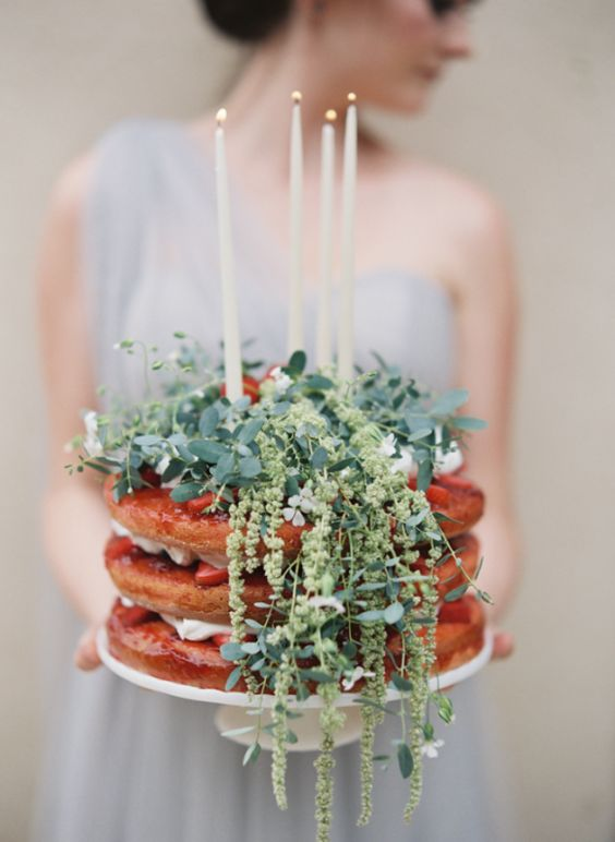 a naked wedding cake with strawberries, fresh greenery and candles on top