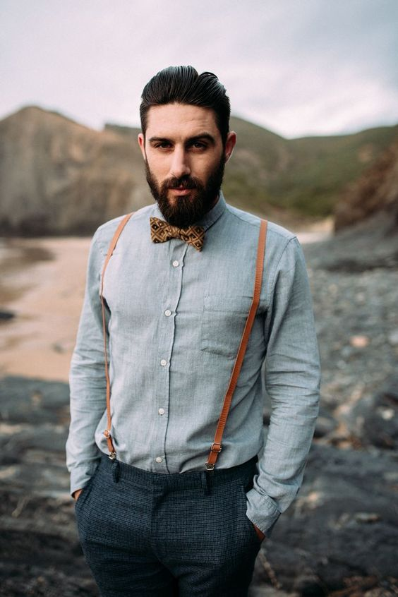 dark grey tweed pants, a light grey shirt, a brown printed bow tie and amber leather suspenders for a vintage feel