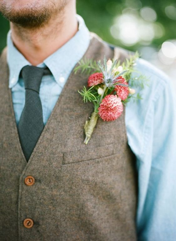 a chambray shirt, a grey tie and a brown waistcoat with a coral bloom boutonniere