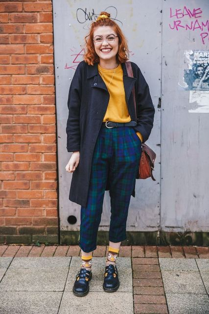 With yellow shirt, funny socks, navy blue coat and bag