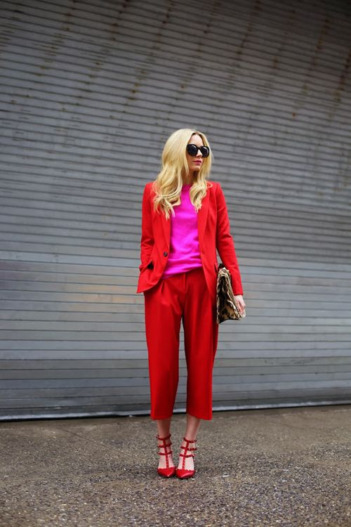 a bold red pantsuit with cropped pants, a pink sweater and red heels for a trendy colorblock look