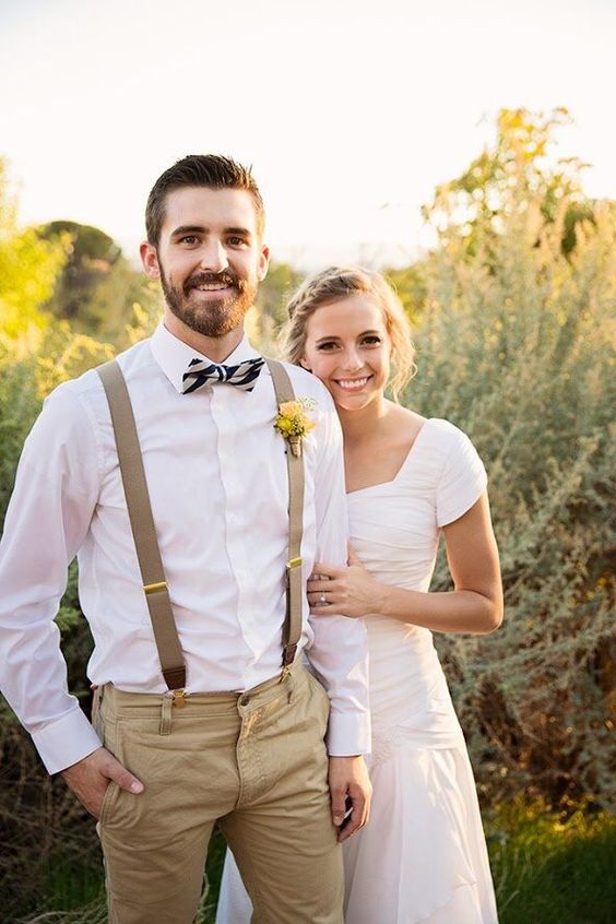 tan pants and suspenders, a white shirt, a striped bow tie and a bold yellow boutonniere for a relaxed look