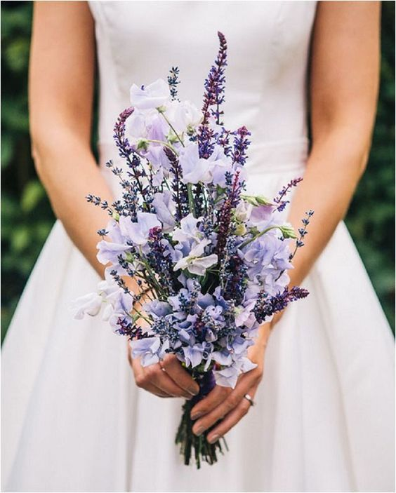 a spring wedding bouquet of lavender and lilac flowers and of a vertical shape looks interesting