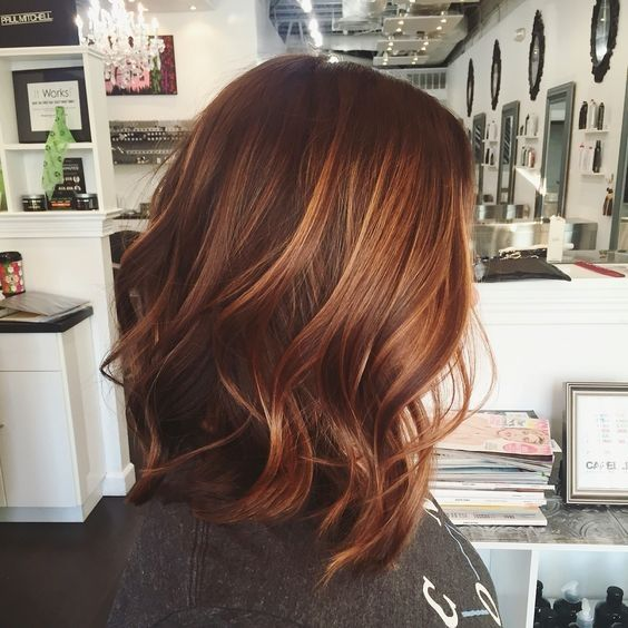 red wavy hair with lighter fiery orange balayage that makes the look bolder
