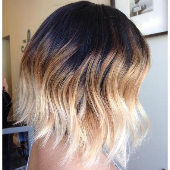a black roots, bronde and then blonde hair with waves