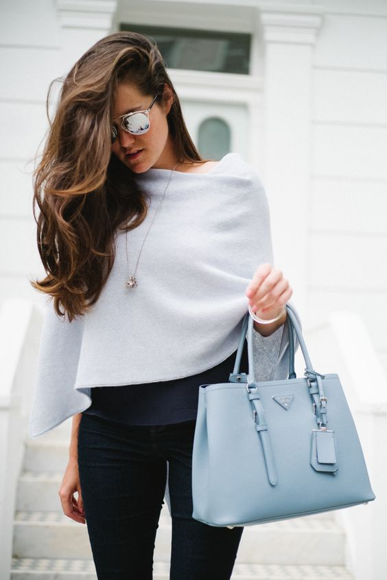 navy jeans, a powder blue bag and a light blue asymmetric poncho over a black top