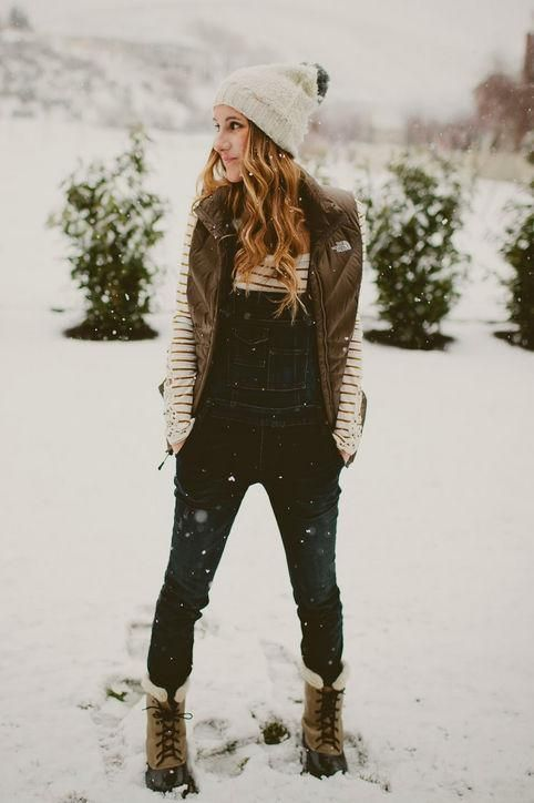 a striped top, a denim overall, a puff vest, snow boots and a beanie