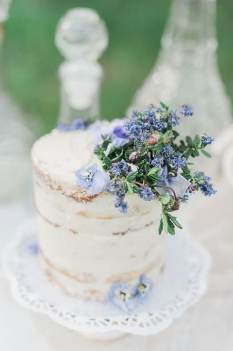 a semi-naked wedding cake decorated with blue flowers and foliage looks ethereal