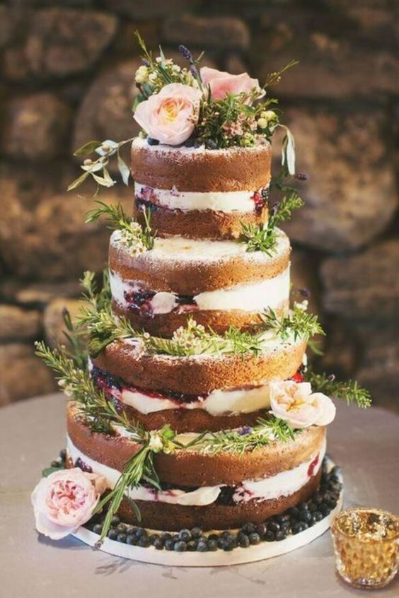 a naked wedding cake decorated with blueberries, fresh herbs and some blooms for a rustic feel