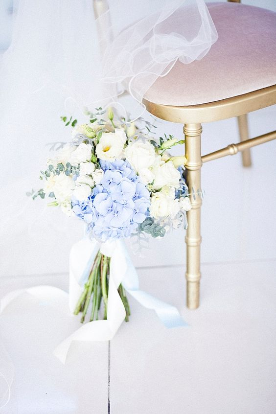 a beautiful bouquet of white blooms and blue hydrangeas, eucalyptus and with blue ribbons