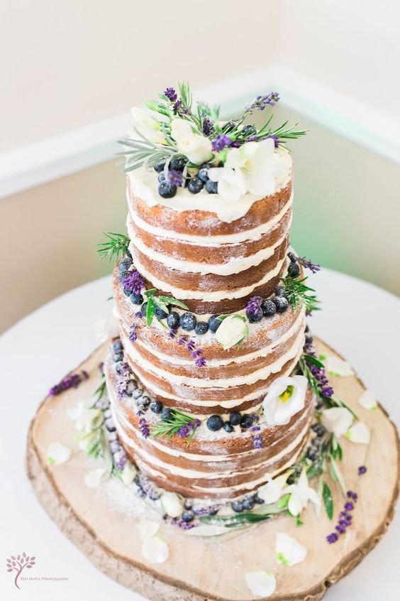 naked spring wedding cake topped with blueberries, lavender and some white blooms