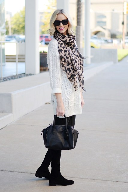 With white sweater dress, black tights, high boots and black small bag