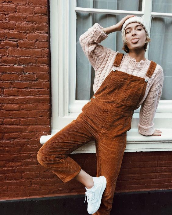 a cable knit neutral sweate and beanie, a rust-colored overall and white sneakers
