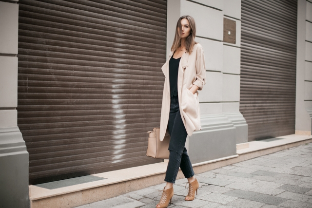 With black shirt, jeans, brown shoes and beige bag