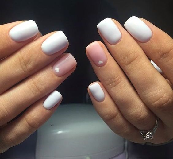 white matte nails with a blush accent and little white hearts on them
