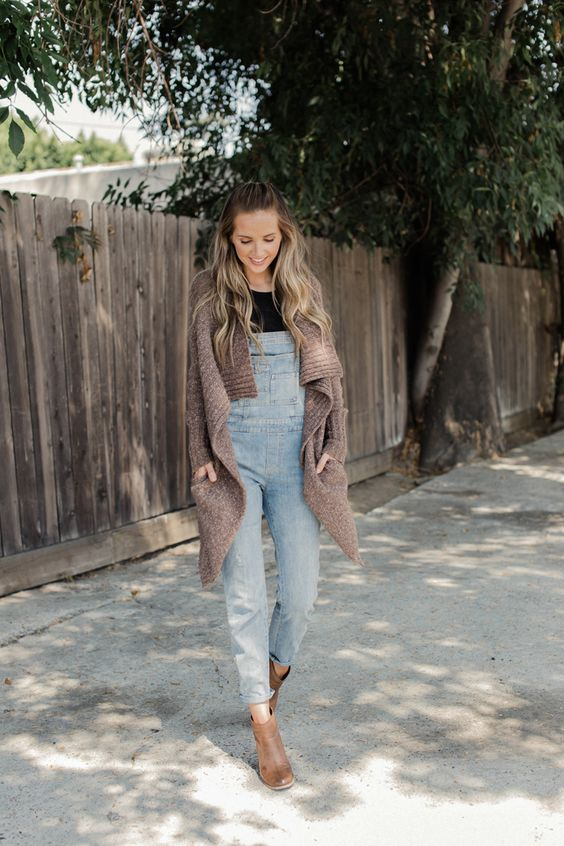 a black tee, a denim overall, a brown cardigan and brown booties