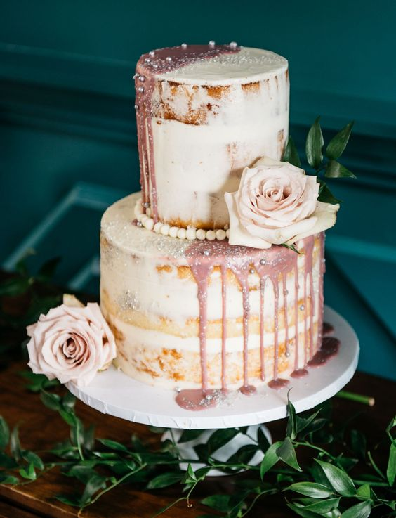 a naked wedding cake with dusty pink dripping, blush blooms and edible pearls for an elegant touch