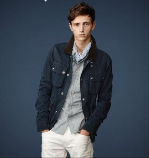 With gray button down shirt, navy blue jacket and white pants