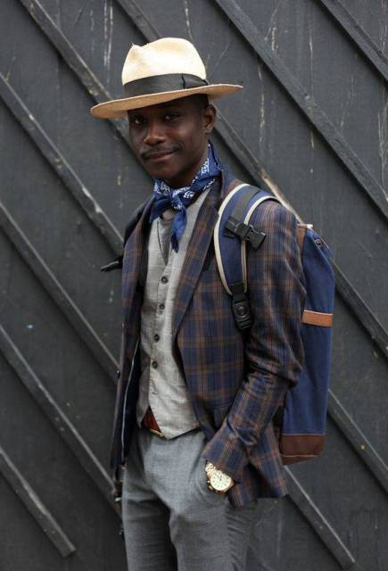 With gray vest, plaid blazer, gray trousers, hat and backpack