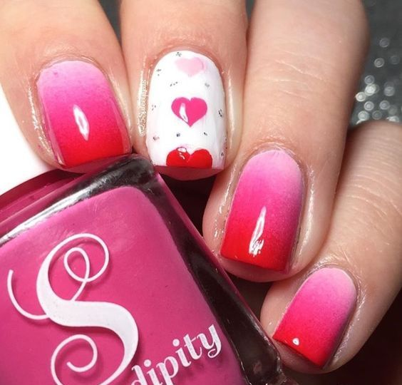 ombre pink to red manicure with a triple heart accent