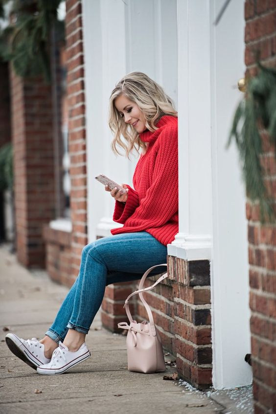 a red chunky knit sweater, blue skinnies, white sneakers and a blush bag