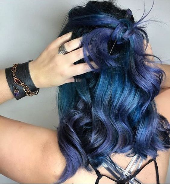 teal wavy hair with cold purple highlights for a trendy touch