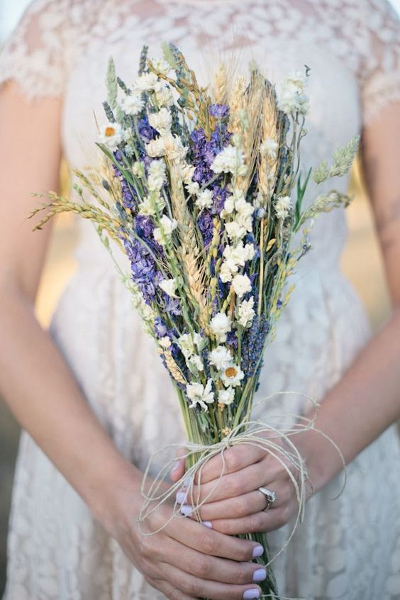 a cool rustic bouquet with wheat, purple delphinium, some dried white blooms