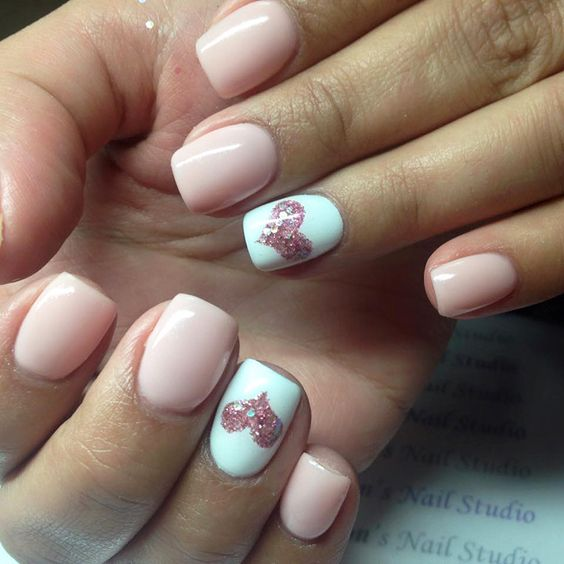 pink manicure with accent white nails and pink glitter hearts on them