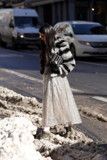 With light gray maxi skirt, black clutch and flat boots