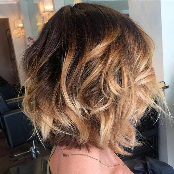 a brown bob with golden caramel balayage highlights and cool waves
