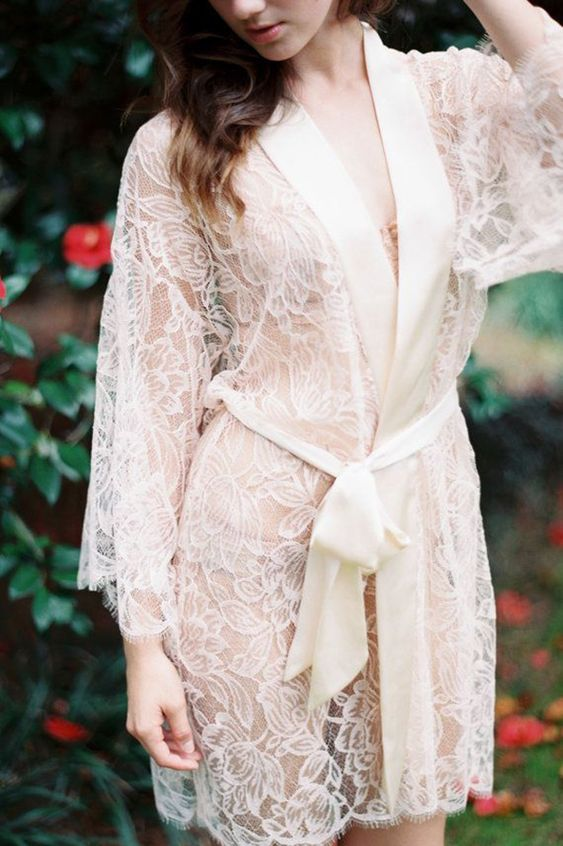 an off-white floral lace short bridal robe with long sleeves, a silk ribbon trim and a matching sash