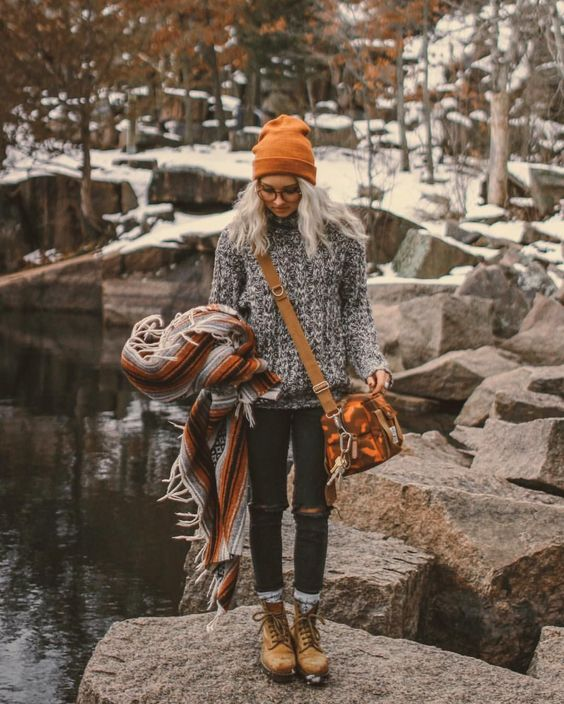 ripped jeans, a chunky knit sweater in black and white, mustard boots, a matching bag and beanie