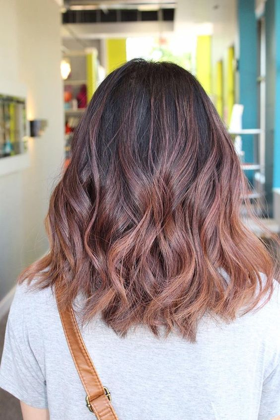 a black base with rose gold balayage with subtle waves looks very chic