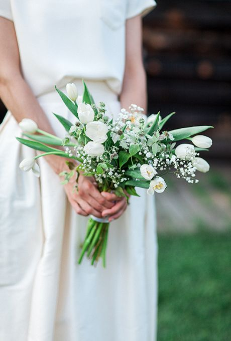 a minimalist bridal bouquet with white tulips, baby's breath, thistles and leaves for a modern bride