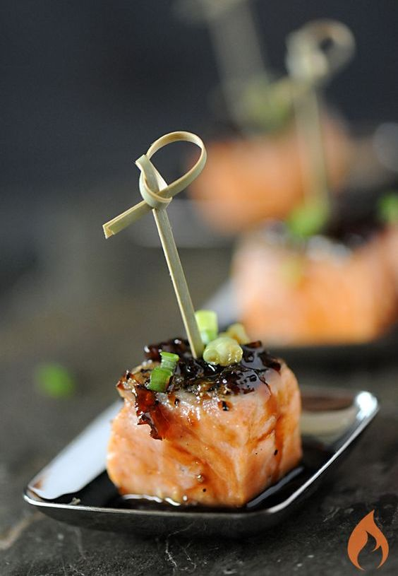 bourbon-glazed salmon appetizer with green onions on skewers