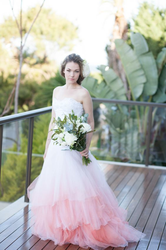 a strapless sweetheart neckline princess-style wedding dress with a ruffled ombre pink skirt