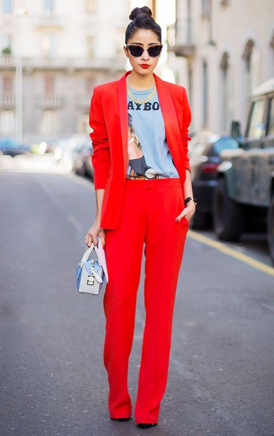a red pantsuit, a printed shirt, a statement necklace and a small bag