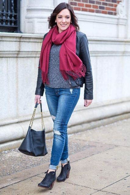 With gray sweater, cuffed jeans, ankle boots, leather jacket and bag