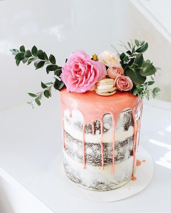 a naked wedding cake with pink drip, vanilla macarons, fresh blooms and foliage