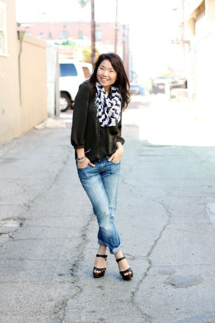 With black blouse, cuffed jeans and platform shoes