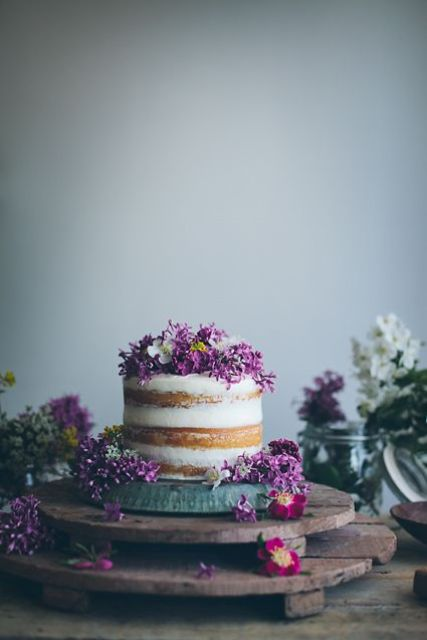 a naked cake topped with lilac and some white blooms for a bold spring look
