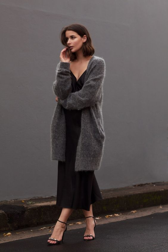 a black slip midi dress, strappy heels and a dark grey cashmere cardigan for a sexy yet comfy look