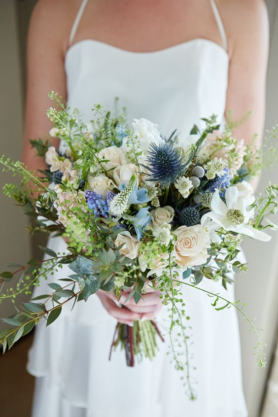 a textural wedding bouquet with blue thistles, white blooms, various greenery looks natural and a bit wild