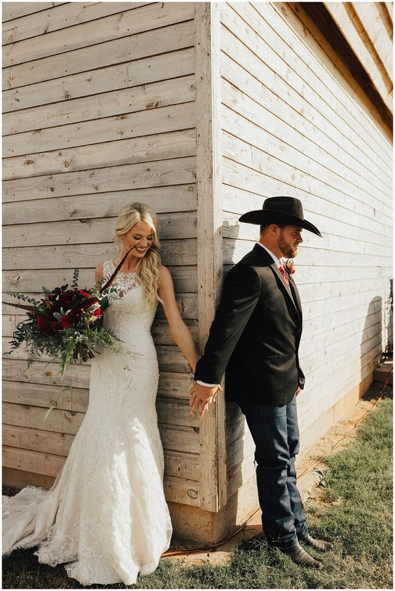 navy jeans, a black jacket, a white shirt, a bold tie and a cowboy hat for a ranch wedding
